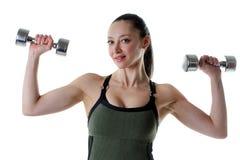 Hembra apta que lleva a cabo un sistema de pesas de gimnasia Imagenes de archivo