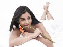 Hembra asiática en cama con una flor Fotografía de archivo