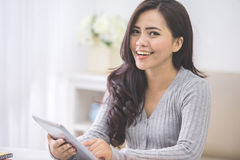 Hembra asiática en casa usando la tableta Imagen de archivo libre de regalías