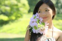 Hembra asiática hermosa con las flores Imágenes de archivo libres de regalías