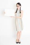 Hembra asiática que sostiene la tarjeta de papel en blanco blanca Foto de archivo libre de regalías