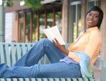 Hembra atractiva del African-American que lee un libro Foto de archivo libre de regalías