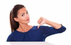 Hembra atractiva en camisa azul con el pulgar abajo Fotografía de archivo libre de regalías