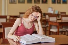 Hembra atractiva joven con el pelo astuto ondulado que se sienta en el escritorio en biblioteca de universidad, estudiante univer imágenes de archivo libres de regalías