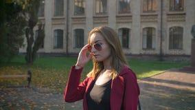 Hembra atractiva joven, estudiante que camina con confianza fuera de la universidad, pelo de fijación y sonriendo en un día solea almacen de video