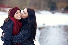 Hembra atractiva que besa a su amigo en la mejilla Imagen de archivo