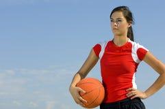 Hembra atractiva que lleva a cabo un baloncesto Imagenes de archivo