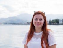Hembra bastante atractiva de los jóvenes con el pelo rojo que mira que camina cerca del mar, día de verano brillante soleado fotos de archivo