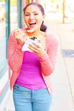 Hembra bonita joven feliz de la raza mixta que come el yogurt congelado Imagenes de archivo