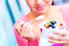 Hembra bonita joven feliz de la raza mixta que come el yogurt congelado Fotografía de archivo libre de regalías