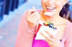 Hembra bonita joven feliz de la raza mixta que come el yogurt congelado Foto de archivo
