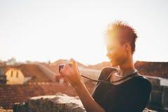 Hembra brasileña con la cámara retra de la foto en el tejado Foto de archivo