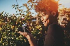 Hembra brasileña con la cámara retra de la foto en jardín Fotos de archivo libres de regalías