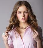 Hembra castaña hermosa en la blusa ligera que se sostiene los pelos Foto de archivo