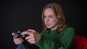 Hembra caucásica adulta del retrato o del primer que juega a los videojuegos con el disfrute dentro almacen de video