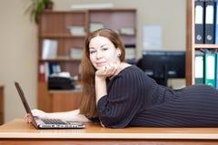 Mujer alegre feliz que pone en el escritorio Imágenes de archivo libres de regalías