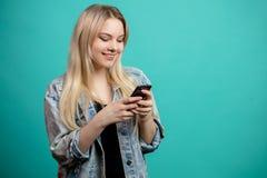Hembra caucásica joven alegre que usa smartphone en azul Imágenes de archivo libres de regalías