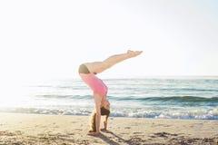 Hembra caucásica joven que hace ejercicios en la playa foto de archivo libre de regalías