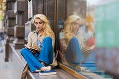 Hembra caucásica magnífica joven con el libro de lectura perfecto de la mirada mientras que se sienta en un travesaño de la tiend Imagen de archivo