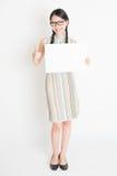 Hembra china que sostiene la tarjeta de papel en blanco blanca Fotografía de archivo libre de regalías
