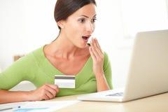 Hembra chocada que usa su tarjeta de crédito para comprar Imágenes de archivo libres de regalías