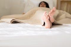 Hembra con descalzo o pies debajo de la manta en el dormitorio por la ma?ana imagen de archivo