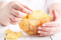 Hembra con el montón de las patatas fritas en plato grande fotos de archivo