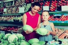 Hembra con el niño que sostiene la col en la sección de las verduras Fotografía de archivo libre de regalías