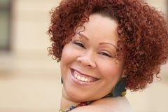 Hembra con el pelo rojo rizado y la joyería brillante Imagenes de archivo