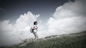 Hembra con el perro del beagle que camina en montañas con las nubes metrajes
