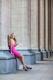 Hembra con el vestido rosado contra una columna Imagen de archivo libre de regalías
