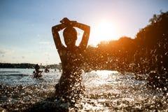 Hembra con estancia perfecta del cuerpo en agua y sol de la toma; Foto de archivo