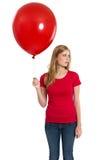 Hembra con la camisa y el globo rojos en blanco Imagenes de archivo