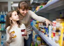 Hembra con la hija que elige alimentos enlatados en tienda de alimentación Fotos de archivo libres de regalías