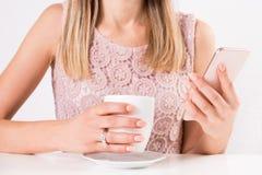 Hembra con la taza en el café a disposición y el teléfono móvil elegante con el vestido del color crema del cordón fotografía de archivo