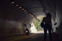 Hembra con una mochila que se coloca en un túnel Fotos de archivo