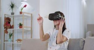 Hembra concentrada con una sonrisa blanca hermosa usando los vidrios de una realidad virtual ella selecciona virtual con el finge