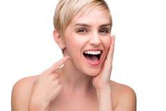Hembra de risa de la diversión linda con sonrisa recta de los dientes blancos perfectos que señala en la boca Imagen de archivo
