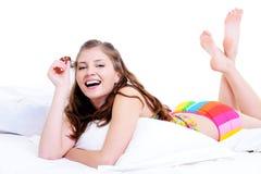 Hembra de risa que miente en cama en la almohadilla blanca Imágenes de archivo libres de regalías