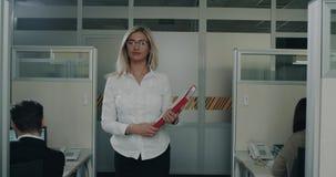 Hembra del administrador de oficinas que camina abajo de la oficina que sostiene un mapa rojo almacen de video