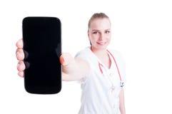 Hembra del doctor o del médico que presenta a pantalla en blanco el teléfono móvil Foto de archivo libre de regalías