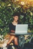 Hembra del negro con el ordenador portátil en el jardín Fotos de archivo libres de regalías