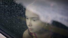 Hembra del niño en el coche en llover almacen de video