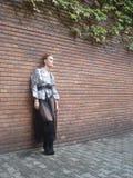 Hembra delante de la pared de ladrillo en patio interno Imágenes de archivo libres de regalías