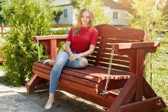 Hembra despreocupada con el pelo recto que lleva el suéter rojo y los vaqueros de moda que se sientan en el banco de madera cómod Imagenes de archivo