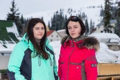 Hembra dos en trajes de esquí y con las gafas del esquí que colocan la nieve-cubierta Foto de archivo libre de regalías