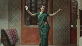Hembra elegante en la sari que realiza danza india