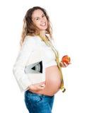 Hembra embarazada con las escalas de la manzana y del peso Foto de archivo