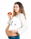 Hembra embarazada con las escalas de la manzana y del peso Fotografía de archivo libre de regalías