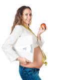 Hembra embarazada con las escalas de la manzana y del peso Fotografía de archivo